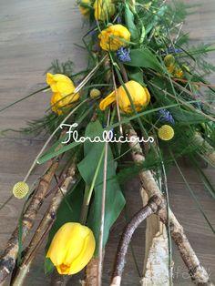 Table arrangement. Made from wood, tulips, craspedia, muscari, asparagus.
