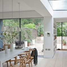 The floor to ceiling glass of this kitchen extension creates a seamless feel between the kitchen/dining area and the outside terrace. The white and wood tonal scheme works well in an open plan kitchen for unity, whilst the trio of pendant lights defines the dining area.  http://www.housetohome.co.uk/room-idea/picture/modern-conservatory-design-ideas-10-of-the-best/8