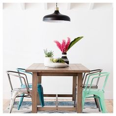 Bring your dining room into the new century with these modern elements. A wooden table mixes with metal dining chairs and concrete planters for an eclectic look. A fresh area rug for spring will ground your room, and a pendant light overhead will illuminate your chic decorating style.