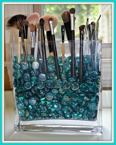 DIY make-up brush holder...so easy, just fill a dollar store clear vase with colored stones and stand brushes up to quickly organize