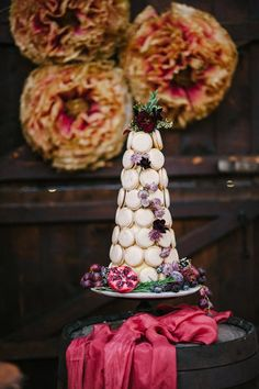 Macaron Tower by Lou Lou Meringues. styled with berries and blooms. Silk runner and giant paper peonies in cranberry and gold by Pompom Blossom.  Lancashire wedding photography. www.gemmamcauleyphotography.com / www.facebook.com/gemmamcauleyphoto