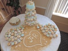 """Jessica Dmyterko did a wonderful job on the cake and display table. She wrote the bride and groom's initials in the """"sand"""" (brown sugar) and the cupcakes were decorated beautifully."""