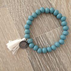 Armband van 8mm mistblauw hout met metalen dubbeltje en wit kwastje. Van JuudsBoetiek, te bestellen op www.juudsboetiek.nl.