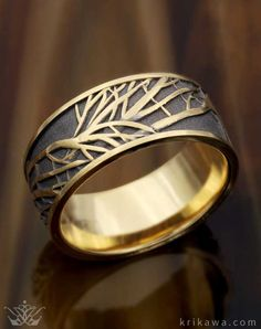 This unique nature wedding band is our Tree of Life Wedding Band in 18k yellow gold with darkened recess. The band measures 10mm in width, Choose your favorite metal and width and will will custom make your dream wedding ring!
