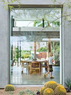 A floor-to-ceiling window frames the dining area of a Canadian family's getaway in Palm Springs, California, renowned for its iconic midcentury architecture and legendary celebrity habitués.