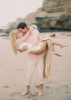 Pink and gold wedding engagement shoot inspiration. Shot on the beach with a mermaid look. Long gold sequin skirt and white tank top for her; long-sleeved pink collared shirt and khaki pants for him.