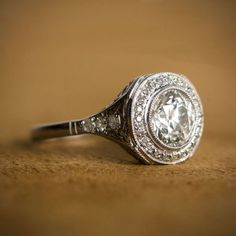 A rare antique engagement rings, surrounded by a halo of diamonds. Circa 1920.