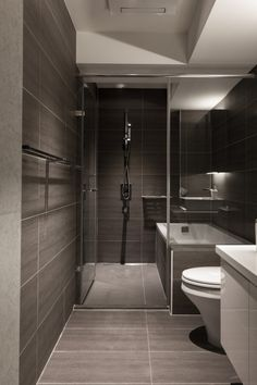 A minimalist bathroom uses a soothing soya bean colored large wall tiles and floor tiles. The white bathroom seating and vanity add a contrast.
