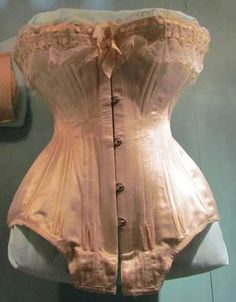 "Silk satin corset with lace and silk grosgrain ribbon trim, ca. 1900. Thrusting the bust forward and the behind back, the turn of the century corset created the sinuous ""S-curve"" silhouette that was then the ideal. This posture was more uncomfortable than corsets of most other periods."