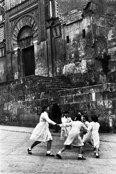 schoolgirls dance in front of the mosque, cordoba, spain , 1954  photo byinge morath/magnum photos/the inge morath foundation