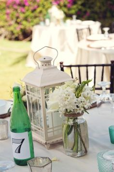 Lantern, mason jar wrapped in burlap or twine with a few simple flowers, and table marker - this is one direction i'm thinking of going with my centerpieces
