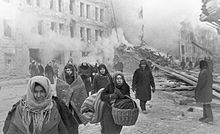 World War II - soviet civillian in Leningrad leaving destroyed houses after a German bombardment of the city 10 Dec 1942