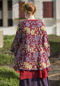 Een schitterend vest met een krioelend, bloeiend dessin in prachtige kleuren. Een jacquardgebreid overslagmodel met strikbandjes, lange mouwen en een contrasterende kleur langs de randen. Natuurlijk met een praktische zak!