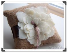 Adorable Burlap Ring Pillow with Ivory Felt and Tulle Layered Flower Accented with Wood Beads and Checkered Ribbon. $25.00, via Etsy.