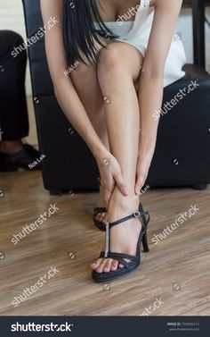 Female legs are wearing fashion shoes of high heels as painful toes. High heels shoe feet pain on the couch in office