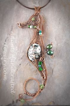 Sea Horse with a Green Tree Moss Agate Gemstone as the Focal Point, Wire-wrapped in Antiqued Copper with a 16 Brown Round Leather Cord included. It is also accented by three Swarovski Crystals, nine Czech glass beads & two fresh water pearls. It is of stunning artisan craftsmanship and a definite sta