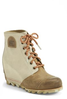 Staying stylish rain or shine with these olive-hue lace up waterproof wedge booties.