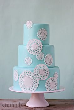Three-tier cake covered with aqua fondant, decorated with different-sized doilies. The eyelets and holes in the doilies are individually punched out using free hand.