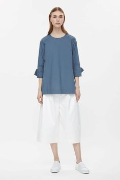 This loose-fit top is made from soft cotton poplin with oversized folded cuffs and split sides. Flaring towards the hem, it has a round neckline, 3/4 sleeves and a hidden press stud fastening on the back.