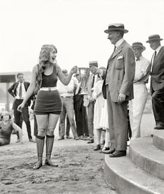 """""""Washington Tidal Basin Beauty Contest -- August 5, 1922."""" Seventeen-year-old Eva Fridell, takes the loving cup from judge Isaac Gans."""