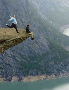 """What the heck is happening in this picture? It is identified as """"Trolltunga"""" Sharp Top Hill - Norway - with no explaination for the man caught in the act of doing something strange (and fatal). Places Around The World, Travel Around The World, Around The Worlds, Just Dream, Exotic Places, Cool Pictures, Amazing Photos, Amazing Photography, Places To See"""
