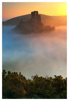 evocativesynthesis:Corf Castle sunrise (by Sebastian Kraus) enchantedengland: Corfe Castle, Dorset, Engand, is a fortification built by William the Conqueror, which signifies that it is very very anciently old. It looms above a lovely village of the same name, although no one pays attention to the village because LOOK AT THIS.