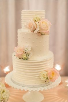 classic white wedding cake with rose accents