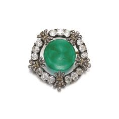 Emerald and diamond brooch, late 19th century Set with a cabochon emerald within a frame of cushion-shaped and circular-cut diamonds, highlighted with fleur de lys motifs set with single-cut and rose diamonds