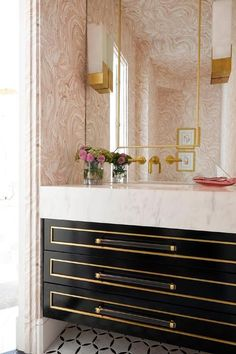 Contemporary pink and black powder room boasts a black and gold floating washstand finished with brass and lucite pulls and a thick white marble countertop.