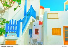 Colorful Architecture of Mykonos, Greece - Mykonos lies in the middle of the Cyclades islands and a popular tourist destination. It is a great place to enjoy the pictoresque architecture - whitewashed houses with blue rooftops, with red flowers intensifying the blue doors and windows.