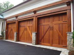 Garage Doors - Nice detail all around here! Beautiful wood doors and trim mixes well with the texture of the stone bases and edging.