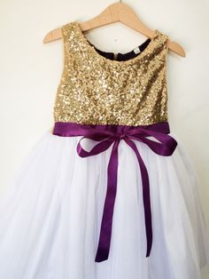 Gold sequined flower girls dress with white or ivory tulle skirt and purple satin ribbon. Perfect for a wedding attend dress, flower girl dress, Birthday Dress or to attend semi formal to formal occasion like Christmas Party, etc.. Now you can choose true white tulle or ivory tulle for the skirt. If you want to have a different color of ribbon please let me know  Custom Order Size: Please provide your child measurement: Chest and specific length otherwise you can also choose from my standard…