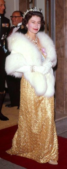 1963. Queen Elizabeth II matches her sparkly gold dress to her pumps as she exits an event at a London hotel in 1963.