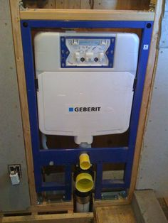 Geberit in-wall tank and frame unit roughed in with supply and waste plumbing connected, ready for wall finishing over the unit.