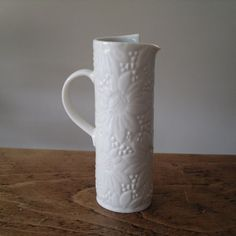 A handbuilt jug made from porcelain clay. Decorated with an all over flower pattern impressed into the clay. Simply glazed inside in a celadon blue, clear on the outside