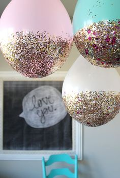 Glitterized Balloon Garland | A balloon garland adds instant festivity to any party affair, but this idea makes the garland particularly celebratory! Pick out some sequins, glitter, chunky glitter, and mod podge at your local craft store, and go to town. The glittery end of the balloon is automatically heavier than the top, so these look great strung together as a high (ceiling?) garland.