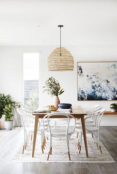 Gorgeous Scandinavian dining room with warm wood paired with cool with and natural woven pendant light. Love the pops of blue