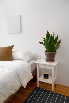 white bedside table with plant