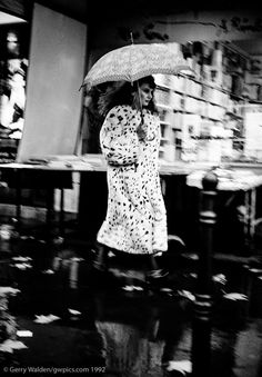 A young lady in a fur coat rshes through the rain on a street in central  Paris - taken from a passing taxi cab.