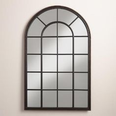 Our window-inspired iron mirror features a broad arch and an aged black finish, lending fluid shape and industrial edge to your wall.