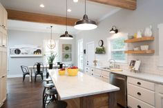 "As seen on HGTV's ""Fixer Upper,"" lighting, counters, wood island, white dining table, dark chairs"