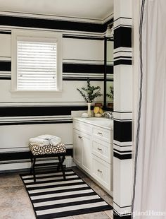 Chic black and white bathroom with black and white horizontal striped wallpapered walls featured in @New England Home via Decor Pad. #peacocklove #polkadotpeacock #blackandwhite