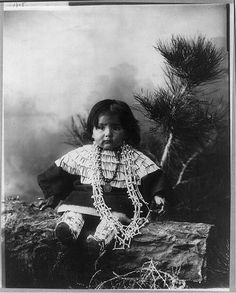 Small Indian child seated on log (wearing miraculous medal).