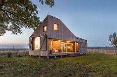 Een architectenbureau uit Praag bouwde een fijn en duurzaam huis midden in de natuur van Tsjechië. De luiken kunnen helemaal open voor een prachtig uitzicht.