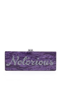 A swirling acrylic Edie Parker clutch with glittering 'Notorious' script across the front. Kiss-lock clasp and hinged construction. Unlined interior with mirror panel. Dust bag and microfiber polishing cloth included.