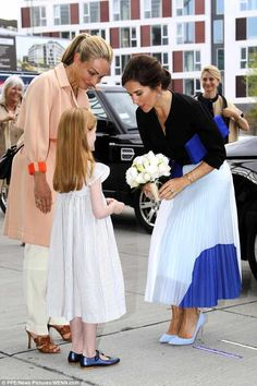 The ever elegant mother-of-four where she was met with a young girl who presented her with...