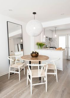 Open floor plan dining room with circular table and circular hanging light fixture | RTG Designs