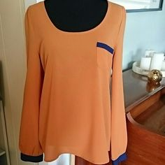 Edge | Orange & Navy Blouse Adorable blouse by Edge. Long sleeves, blue trim, breast pocket, buttons down back. This is in overall excellent condition but with one small flaw...a stain on the back/underside of one upper sleeve.(see 4th pic) Edge Tops