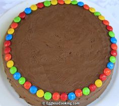Arrange M&Ms around the circumference of the top-level cake.