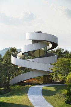 Two curving staircases encircle the exterior of this wedding chapel,  meeting at a rooftop platform that overlooks the Hiroshima coastline